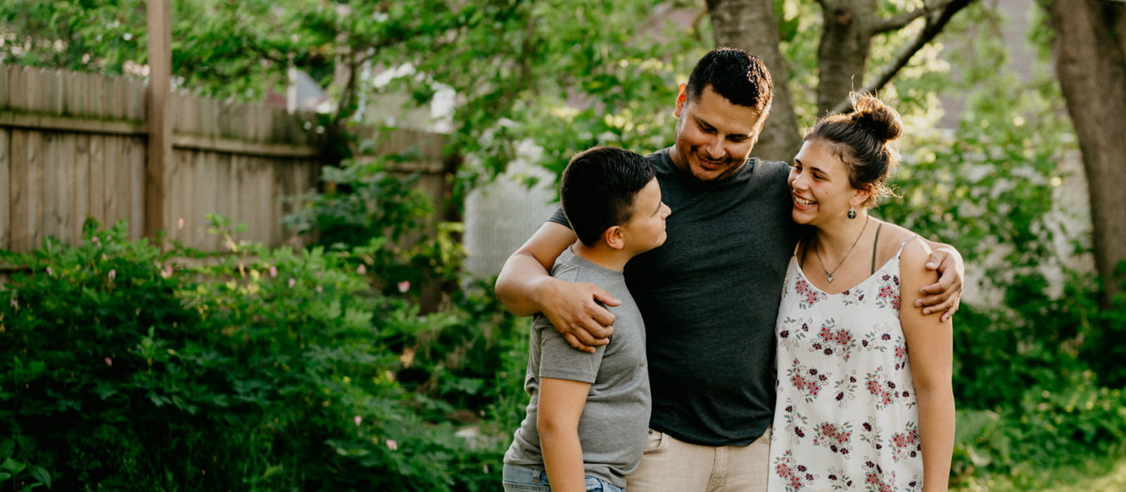 Family standing in yard smiling at each other.